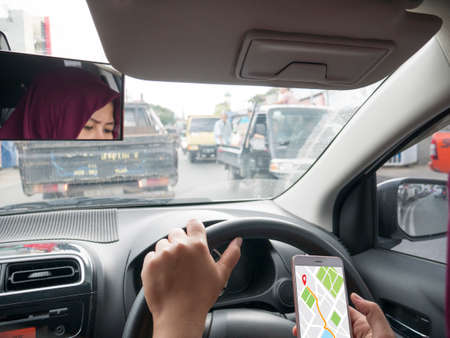 Car driver using smart phone with GPS map navigation while driving, car sharing app concept Imagens