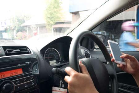 Schließen Sie das Bild eines Fahrers, der beim Autofahren eine Nachricht auf dem Smartphone liest, ein gefährliches Verkehrssicherheitsunfall-Autoversicherungskonzept Standard-Bild