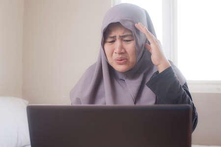 Smutna muzułmańska kobieta płacze wyrażenie, aby zobaczyć zły raport finansowy na laptopie, strata w koncepcji giełdy