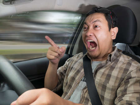 Portrait of Asian male driver mad of other car criver, speeding his car with anger dangerously,  mischievous reckless way of driving concept with motion blur Stok Fotoğraf