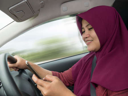 Female Asian driver reading message on smart phone while driving a car, dangerous traffic safety accident crash car insurance concept Imagens