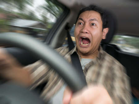 Portrait of male Asian driver shocked and panic about to have crash accident, zoomed motion blur defocus concept