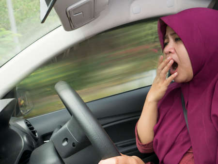Female Asian muslim driver sleeping while driving a car, dangerous traffic safety accident crash car insurance long trip tired concept Stock Photo