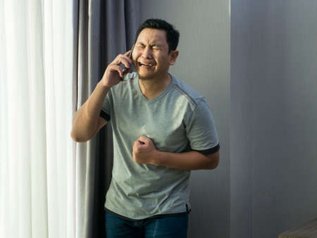 Portraot of young Asian man crying to get bad news on phone, sad crying expression