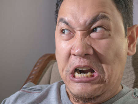 Angry young Asian man looks really mad of something bad. Close up head and shoulders