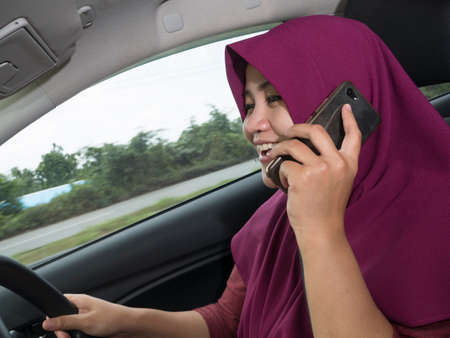Female Asian muslim driver making a call while driving a car, dangerous traffic safety accident crash car insurance concept