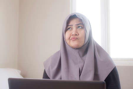 Portrait of Asian muslim businesswoman working on laptop at home, with thinking gesture, confused looking for solution of a problem Фото со стока