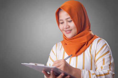 Portrait of beautiful young Asian muslim woman writing something, successful businesswoman checking records 版權商用圖片