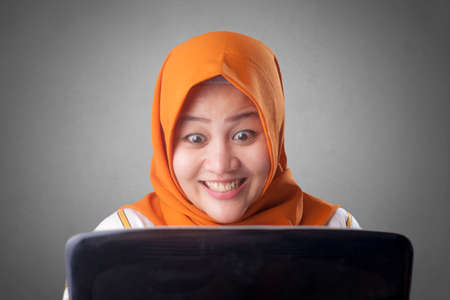 Portrait of Asian muslim lady shows happy surprised expression celebrating winning victory gesture after receiving good news on her email