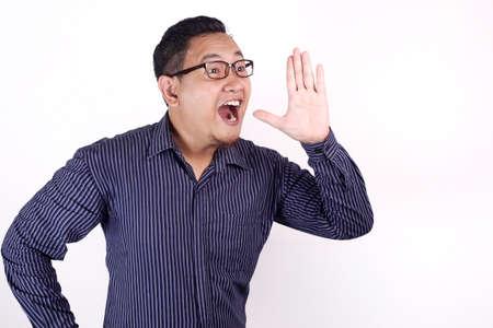 Portrait de jeune homme d'affaires asiatique parlant à voix haute, sur fond blanc avec espace pour copie Banque d'images