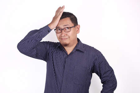 Funny young Asian businessman shows regret gesture, hits his forehead, agains white background