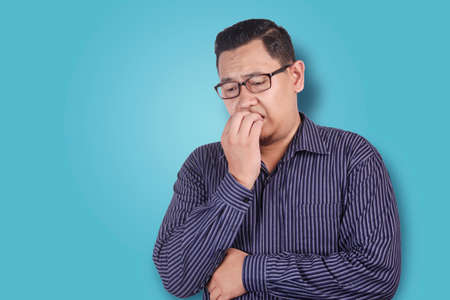 Portrait of young Asian man looked worried or nervous of something bad, look down and biting his nails Stock fotó