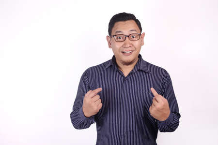 Portrait of young Asian man smiling while pointing himself with surprised expression, can't believe to be choosen