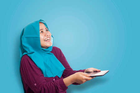 Portrait of Asian muslim woman surprised and smiling happy to see something above when using her smart phone with copy space Banco de Imagens