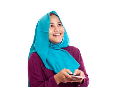 Portrait of Asian muslim woman surprised and smiling happy to see something above when using her smart phone with copy space Imagens