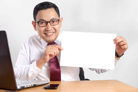 Portrait of happy smiling successful Asian businessman shows white paper, template copy space mock up concept