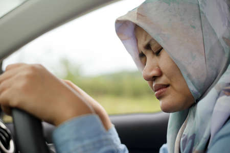 Portrait of sad muslim lady crying while driving her car, driver in problem concept Stock Photo