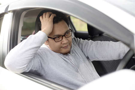 Portrait of funny Asian male driver get bored in his car trapped in traffic jam, tired lazy facial expression gesture 스톡 콘텐츠