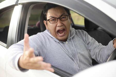 Portrait d'un conducteur asiatique devenant fou et en colère à cause de la circulation, criant et pointant du doigt sa voiture