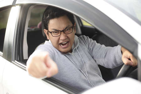 Portrait of Asian male driver getting mad and angry from the traffic, screaming and pointing from his car