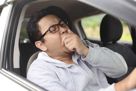 Portret van een yung Aziatische mannelijke bestuurder die geeuwt vanwege slaperig moe tijdens het rijden in een auto, gevaar verkeersongevallenverzekeringsconcept
