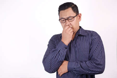 Portrait of young Asian man looked worried or nervous of something bad, look down and biting his nails Imagens