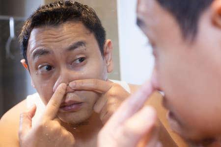 Retrato de atractivo joven asiático exprimiendo el acné en su nariz, reflejo de espejo en el baño Foto de archivo