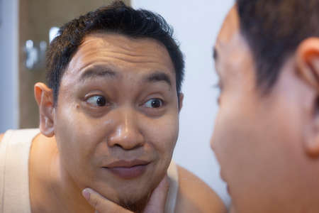 Portrait of funny attractive young narcissist Asian man smiling happily while looking at himself in mirror
