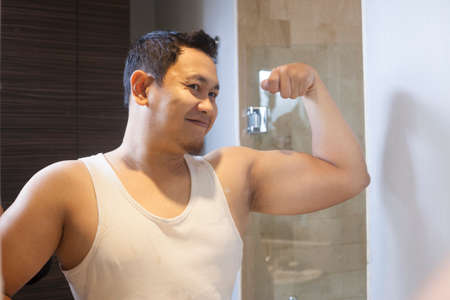 Portrait of funny attractive young narcissist Asian man smiling happily while looking at himself in mirror, biceps arm muscle posing, feeling strong concept