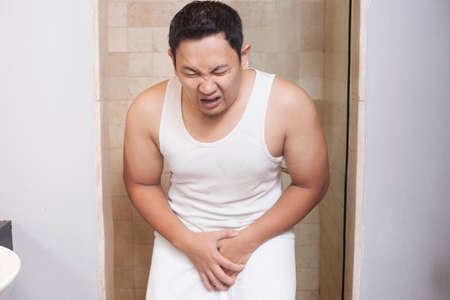 Portrait of young Asian man having pain problem in his genital area, urinary problem concept