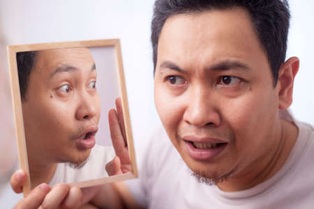 Portrait of young Asian man worried by his inner voice, self confidence problem concept Standard-Bild