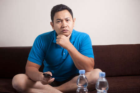 Portrait of funny Asian man watching TV while siiting on couch with some food