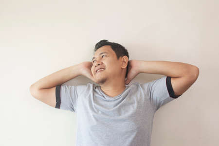 Photo image of young Asian man looked happy, thinking and looking up, hands behind head, having good idea. Half body portrait against grey wall with copy space