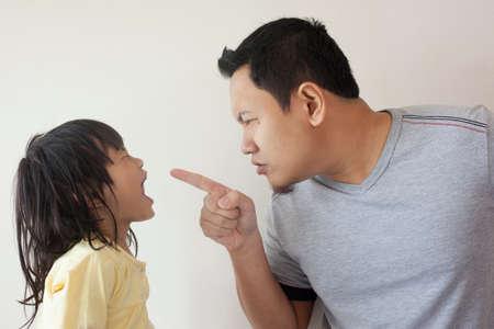 Junger asiatischer Vater und kleine Tochter, die sich streiten, schreien, Vater wütend auf sein Kind?