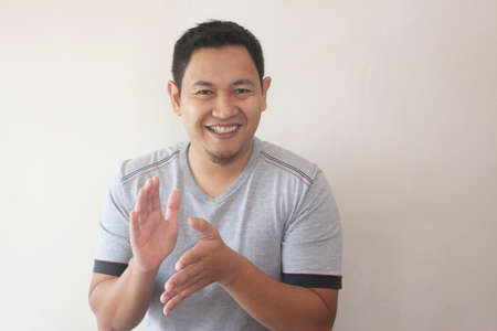 Young Asian man wearing white shirt, happy proud clapping gesture.Over grey background, halfl body portrait