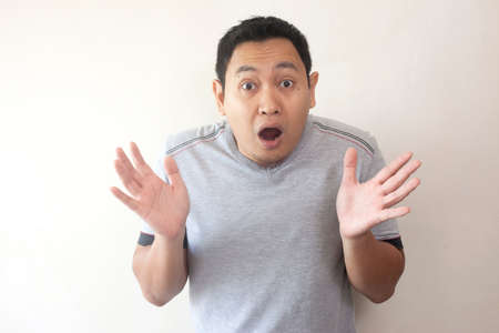 Portrait of Young asian men in casual grey shirt, shocked gesture with open mouth. Hands rised up