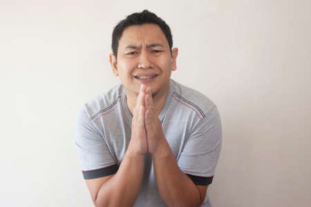 Young Asian man wearing casual grey shirt regret, apologize gesture. Close up body portrait
