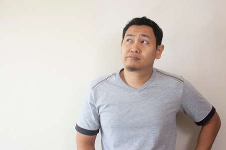 Photo image of young Asian man looked happy, thinking and looking up, having good idea. Half body portrait against grey wall with copy space Reklamní fotografie