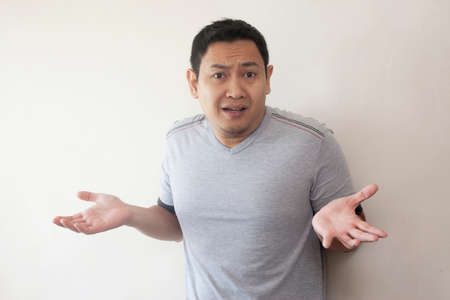 Portrait of funny young Asian man showing unhappy face, looking up with both of his palms open, shrug shoulder up, showing i don't know, rejection or denial gesture Foto de archivo