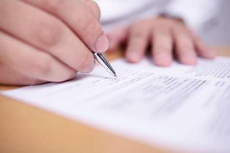 Close-up beeld van zakenman die contract ondertekent of student met examentest, selectieve focus