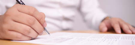 Close up image of businessman signing contract or student having exam test, wide view with selective focus Banco de Imagens