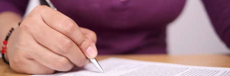 Close up image of businesswoman signing contract or female student having exam test, wide view with selective focus