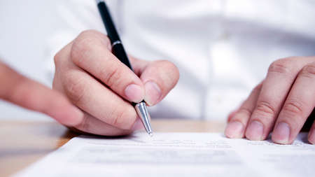 Close up image of businessman signing contract with selective focus