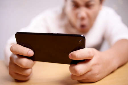 Photo image portrait of a cute handsome young Asian man with funny face playing games on tablet, sad angry loosing expression