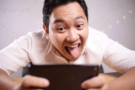 Photo image portrait of a cute handsome young Asian man with funny face playing games on tablet smart phone Banco de Imagens