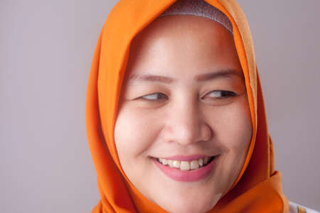 Young Asian muslim woman wearing hijab, smilling happily with expression over grey. Close up head and shoulders Banco de Imagens