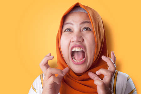 Portrait of Asian muslim lady wearing hijab shows angry screaming gesture