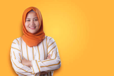 Successfull happy Asian muslim woman wearing hijab smiling friendly with arms crossed, confident strong gesture