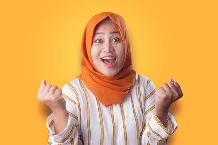 Portrait of success beautiful muslim businesswoman wearing hijab showing winning victory gesture over orange background Banco de Imagens