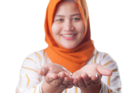 Portrait of Asian muslim lady wearing hijab smiling and shows something in her empty hands, presenting offering copy space template concept